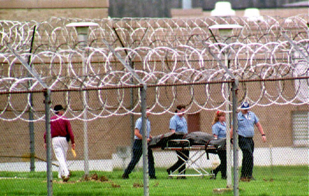 Paramedics remove the body of a prison guard held hostage at the Southern Ohio Correctional Facility in Lucasville, Ohio, on April 15, 1993. Photo: Eugene Garcia/AFP/Getty Images